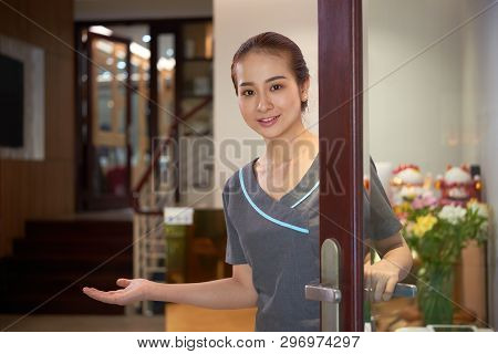 poster of Smiling Young Asian Beauty Salon Worker Opening Door And Gesturing Hand While Inviting Guests In Bea
