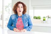 Middle age senior woman with curly hair wearing denim jacket at home afraid and shocked with surpris poster