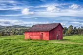 A Red Barn On A Field Landscape In The New England Town Of Cornwall Connecticut On A Blue Sky Day. poster