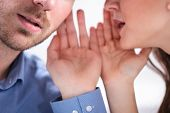 Portrait Of Happy Woman Whispering Secret Or Interesting Gossip To Handsome Man In His Ear poster