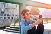 Young beautiful woman holding smartphone and listening to music with wireless headphones. Cheerful s poster