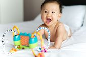 Asian Cute Baby Crawling And Playing Toy On Bed At Home. Baby Is Smiling And Feeling Happy With It.  poster