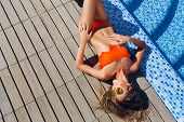 Attractive Blonde Girl With Long Hair Is Lying On Flor Near Pool. She Wears Orange Bikini, Sunglasse poster