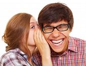Pretty girl talking secret to young man in his ear, man laughing over isolated white background
