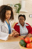 Caregiver Wearing White Jacket Measuring Pulse For Woman poster