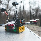Fpv Drone Lies On The Table. The Pilot Sets Up His Racing Drone Before The Flight. poster