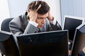 foto of young men  - Image of businessman touching his head while looking at monitor with tired expression - JPG