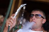 stock photo of shisha  - Man is smoking shisha in an arabic cafe - JPG