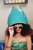 stock photo of pouting  - Pouting lady with frizzy hair sitting under hair dryer - JPG