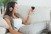 Woman lying on the sofa and listening to music with a red wine glass in the living room