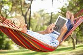 stock photo of rest-in-peace  - Senior Man Relaxing In Hammock With  E - JPG
