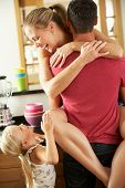 stock photo of interrupter  - Romantic Couple Hugging In Kitchen Being Interrupted By Daughter - JPG