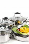 stock photo of dutch oven  - Stainless steel pots and pans isolated on white background with vegetables - JPG