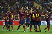 KUALA LUMPUR - AUGUST 10: FC Barcelona's players (maroon/blue) celebrate a goal scored against Malay