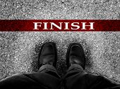 pic of winner man  - Finish line with businessman wearing dress shoes as metaphor for finishing work as a winner - JPG