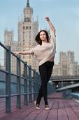 stock photo of ballet barre  - A young woman is standing in a ballet position using as a barre the railing on the waterfront - JPG