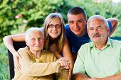 stock photo of visitation  - Happy family visiting the grandmother in the garden of the nursing home - JPG