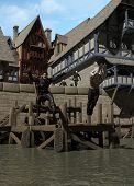 stock photo of rogue  - Two Medieval rogues escaping from the town guard by jumping from the docks - JPG