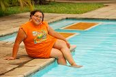 stock photo of fat woman  - Beautiful overweight Hispanic woman sitting by the pool - JPG