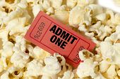 stock photo of matinee  - Close up shot of a red movie ticket surrounded by popcorn - JPG