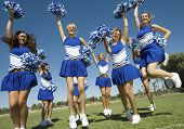 Excited young cheerleaders with pompoms cheering on field