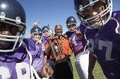 foto of trophy  - Portrait of happy football team and coach with trophy celebrating victory on field - JPG