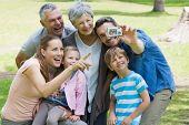 stock photo of extended family  - Man taking picture of his cheerful extended family at the park - JPG