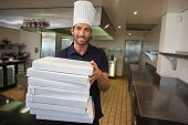 Smiling pizza chef holding stack of pizza boxes in a commercial kitchen
