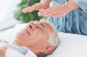 stock photo of reiki  - Massage therapist performing Reiki over senior man at health spa - JPG