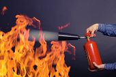 pic of firefighter  - Male hand with a fire extinguisher extinguish the fire - JPG