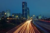 View of Ayalon highway, light traces and modern buildings in evening at downtown of Tel Aviv, Israel