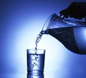 stock photo of pitcher  - Pour water from  pitcher into  glass - JPG