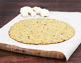 foto of crust  - Plain cauliflower pizza crust on a piece of parchment paper on a cutting board - JPG