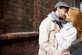 stock photo of amor  - Portrait of amorous couple in stylish clothes outside - JPG