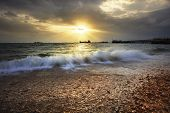 image of sea-scape  - splashing sea wave on gravel beach against sun set sky and commercial ship port - JPG