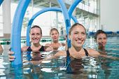 stock photo of day care center  - Female fitness class doing aqua aerobics with foam rollers in swimming pool at the leisure centre - JPG