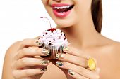 stock photo of finger-licking  - Woman wants to eat a cupcake  - JPG