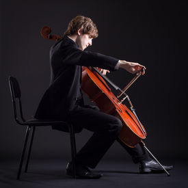 picture of cello  - Cellist playing classical music on cello on a black background - JPG