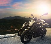 stock photo of motor vehicles  - big bike motorcycle parking on top of mountain with sun light on evening sky background use for sport vehicle extreme traveling and vacation holiday journey - JPG