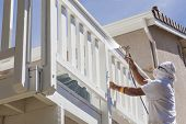 image of facials  - House Painter Wearing Facial Protection Spray Painting A Deck of A Home - JPG