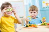 stock photo of little kids  - kids eating healthy food in kindergarten or at home - JPG