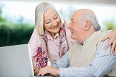 picture of helping others  - Smiling senior couple looking at each other while using laptop at nursing home - JPG