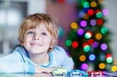 stock photo of indoor games  - Little blond child playing with cars and toys at home indoor - JPG
