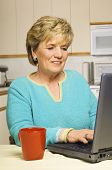 Senior Woman Works On Her Laptop In Her Kitchen, Coffee Mug At The Ready.