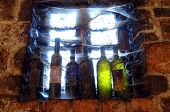 stock photo of cobweb  - Cobweb covered wine bottles in wine cellar on a shelf by the window