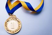 picture of gold medal  - Gold medal in the foreground on yellow blue ribbon - JPG