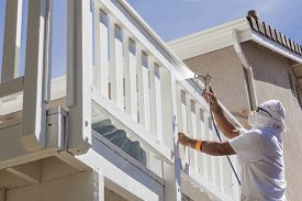 picture of airbrush  - House Painter Wearing Facial Protection Spray Painting A Deck of A Home - JPG
