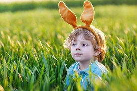 image of bunny costume  - Cute little child with Easter bunny ears playing in green grass on sunny spring day celebrating Easter holiday - JPG