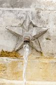 stock photo of gushing  - Detail of a public fountain where sgroga a gush of water - JPG