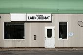 pic of generic  - The front exterior and entrance to an old run-down generic laundromat with sign.